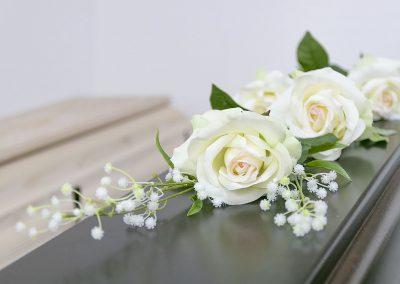 weiße Rosen auf Sarg