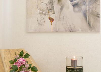 Sarg, dekoriert mit Rosengebinde, daneben Säule mit Kerze